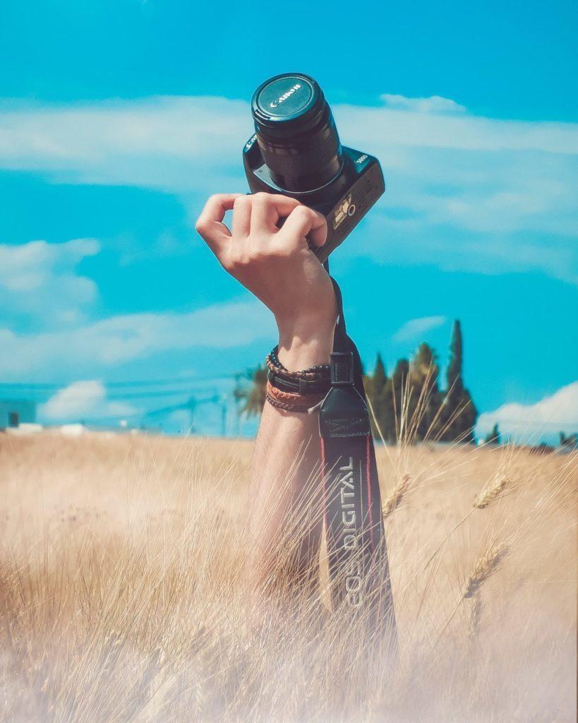 person holding black canon dslr camera kit 1082663 scaled 1